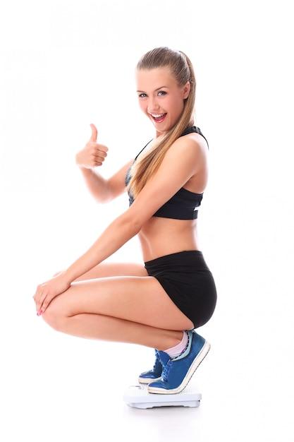 Menina feliz fitness na balança com o polegar para cima Foto gratuita