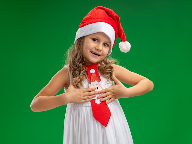 Menina feliz inclinando a cabeça usando chapéu de natal com gravata e colocando as mãos em si mesma, isolada sobre fundo verde Foto gratuita