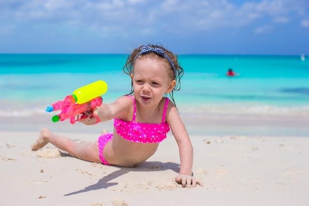 Menina feliz jogando na praia durante as férias do caribe Foto Premium