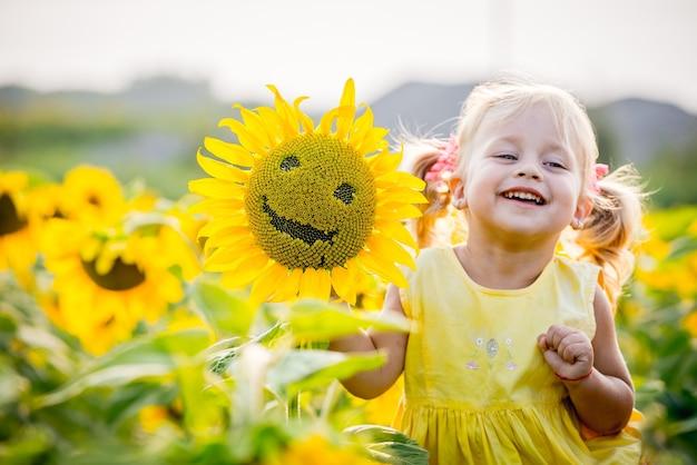 Menina feliz no campo de girassóis no verão. linda garotinha em girassóis Foto Premium