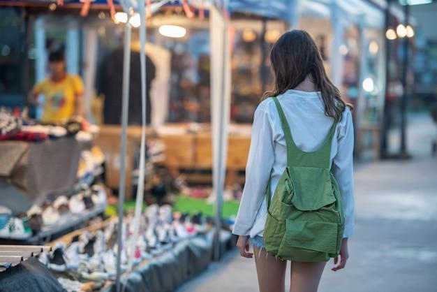 Menina feliz nova asiática com trouxa que anda para comprar no mercado da noite. Foto Premium
