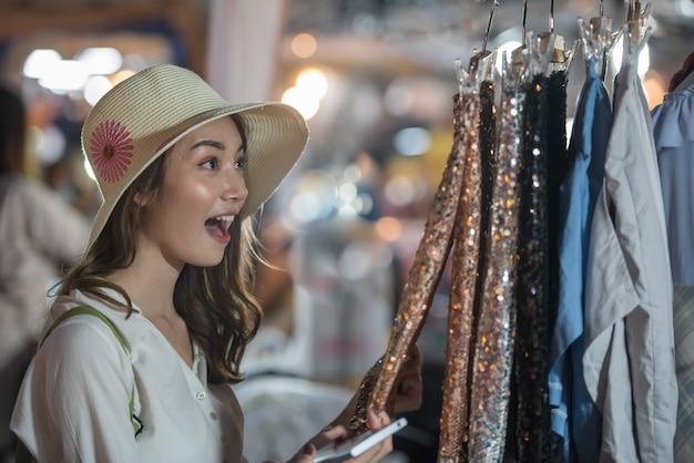 Menina feliz nova asiática que anda para comprar no mercado da noite. Foto Premium