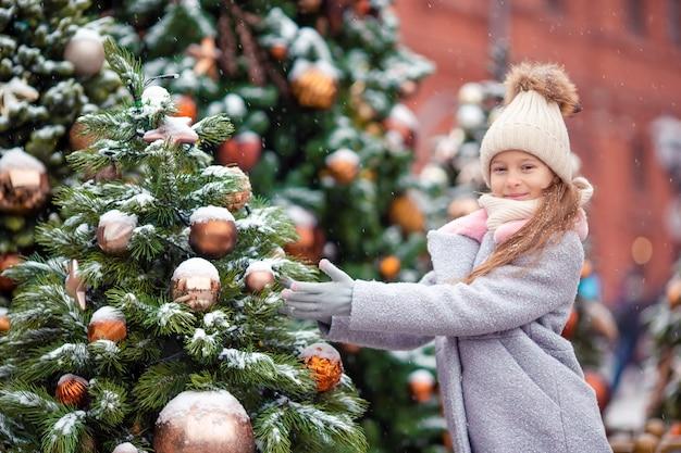 Menina feliz perto do ramo de abeto na neve pelo ano novo. Foto Premium