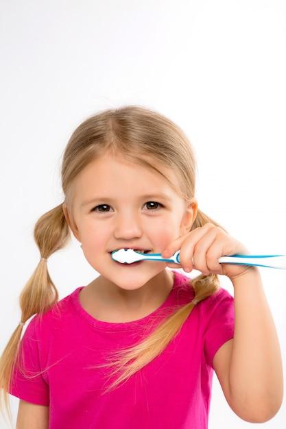 Menina feliz que está com a escova de dentes isolada no branco. Foto Premium