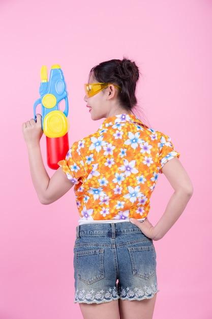 Menina feliz que guarda uma arma de água cor-de-rosa do fundo. Foto gratuita