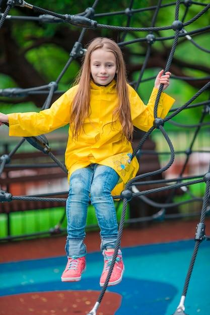 Menina feliz que joga no campo de jogos ao ar livre no dia do outono Foto Premium