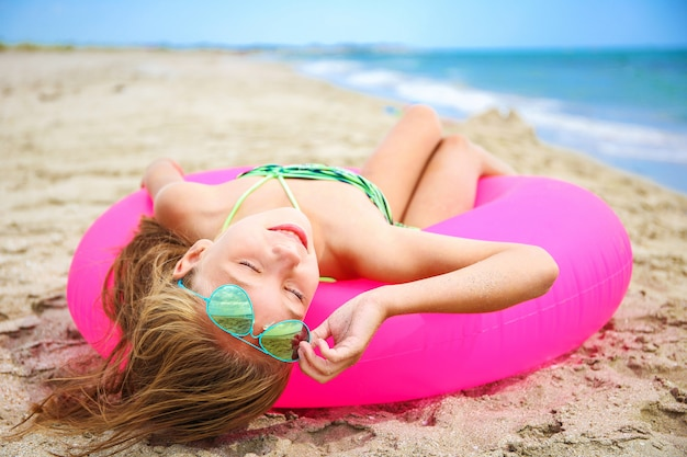 Menina feliz que sunbathing na praia. Foto Premium