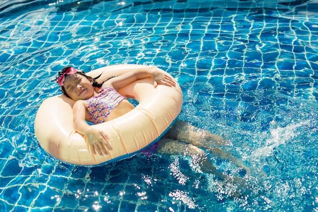 Menina feliz relaxante com anel inflável colorido na piscina ao ar livre em dia quente de verão Foto Premium