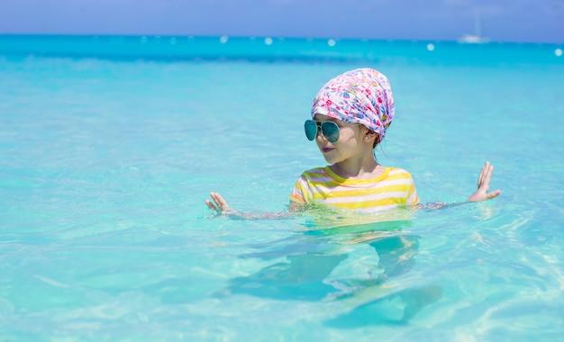 Menina feliz se divertir no mar durante as férias de verão Foto Premium