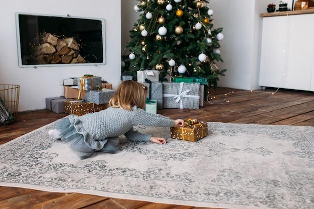 Menina feliz segurando a caixa de presente, árvore de natal. feliz natal e boas festas! Foto Premium
