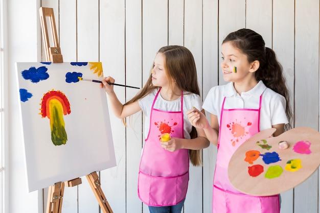 Menina feliz, segurando, paleta, em, mão, olhar, dela, amigo, quadro, ligado, a, cavalete, com, pintar escova Foto gratuita