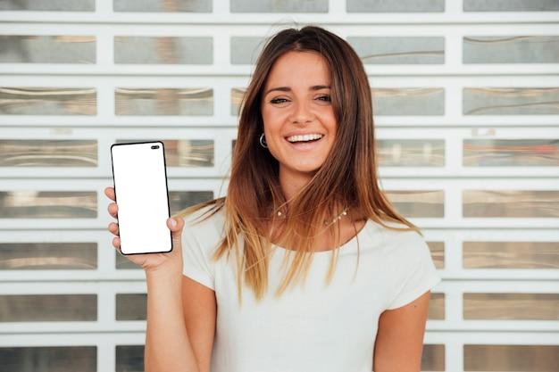 Menina feliz, segurando, smartphone Foto gratuita
