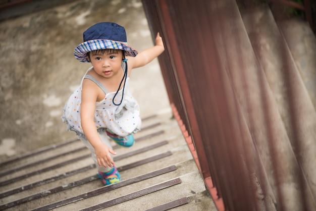 Menina feliz subindo as escadas. kid primeiro conceito passo. Foto Premium