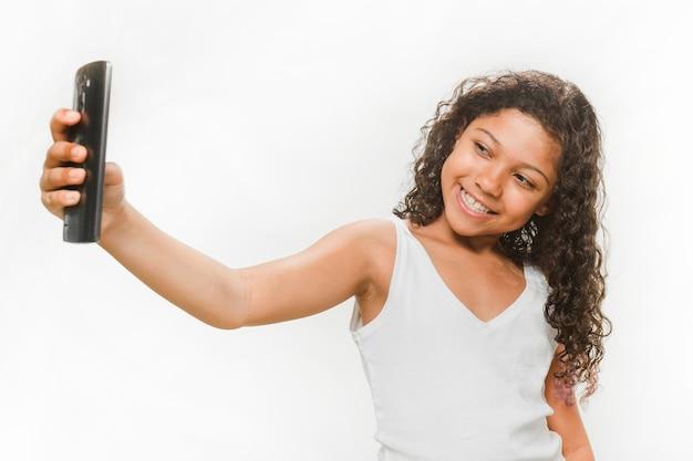 Menina feliz tomando selfie do telefone móvel Foto gratuita