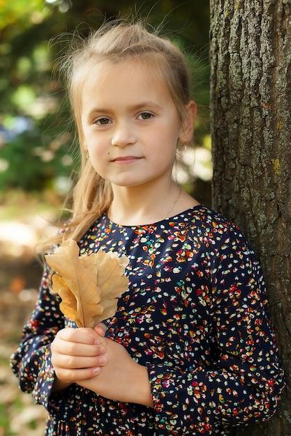 Menina fica em um parque da cidade e segura uma árvore de carvalho fundido. caminhadas de outono. Foto Premium