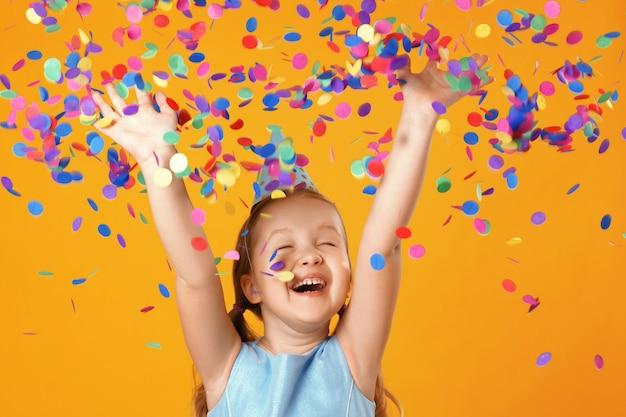 Menina fica sob confetes caindo. Foto Premium