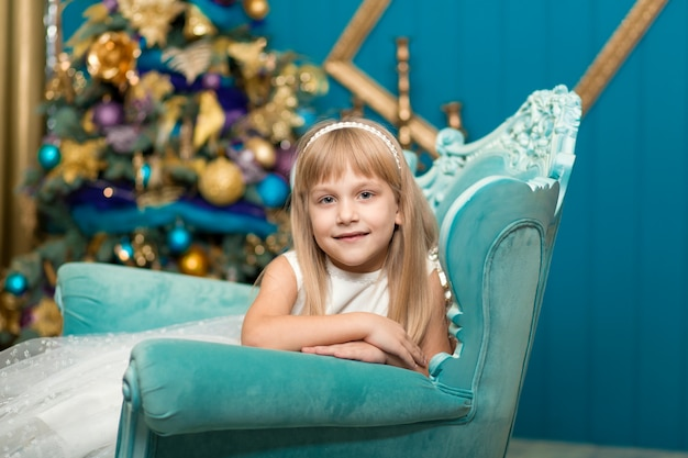 Menina, fingindo estar dormindo em uma poltrona perto de uma árvore de natal para encontrar o papai noel quando ele traz presentes. Foto Premium