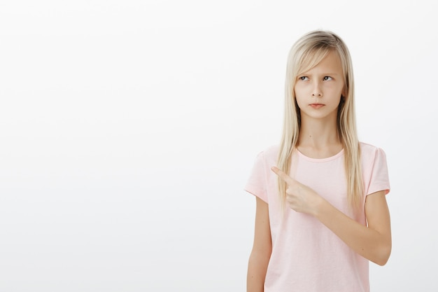 Menina fofa e ofendida com raiva apontando para o canto esquerdo superior, parecendo chateada Foto gratuita