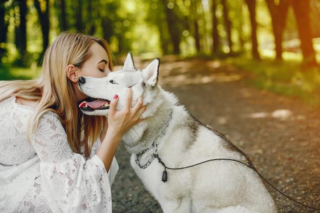 Menina gentil com cabelo claro vestido de branco está jogando junto com seu cachorro Foto gratuita
