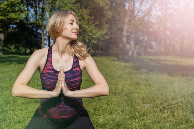 Menina grávida dos jovens que faz a ioga no parque do verão. Foto Premium
