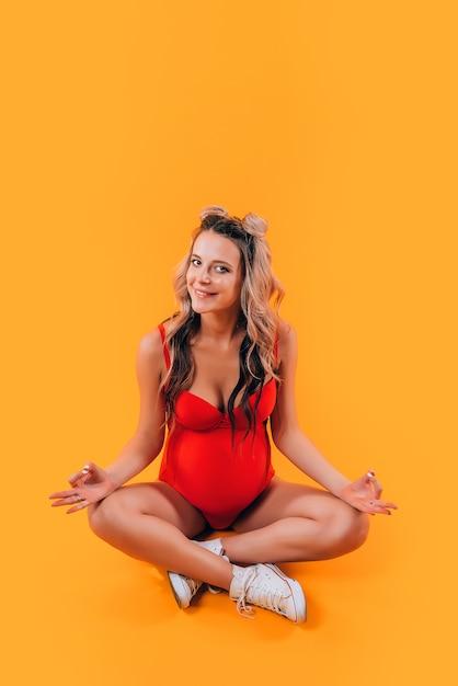 Menina grávida em um maiô vermelho e tênis branco medita Foto Premium
