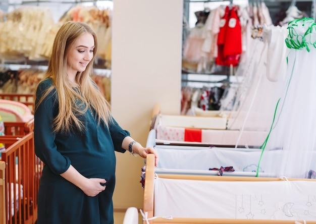 Menina grávida escolhe um berço na loja. Foto Premium