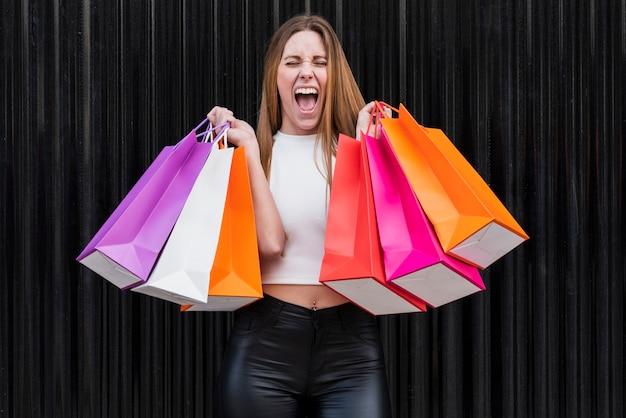 Menina gritando enquanto segura sacolas de compras Foto gratuita