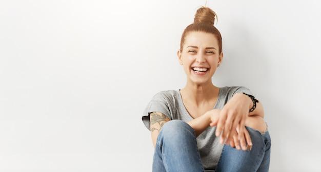 Menina hippie com coque de cabelo usando roupas elegantes, sentada no chão contra a parede branca do estúdio Foto gratuita