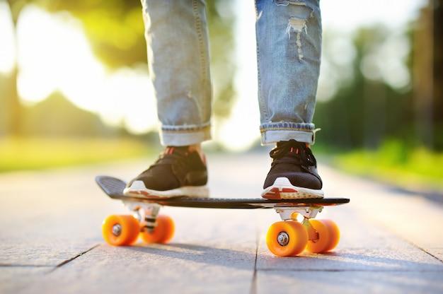 Menina hippie com skate ao ar livre. closeup de skate. mulher desportiva ativa se divertindo no parque Foto Premium