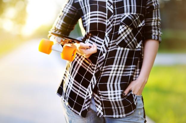 Menina hippie com skate ao ar livre. skate do close up na mão fêmea. mulher desportiva ativa se divertindo no parque Foto Premium