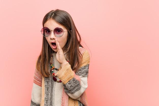 Menina hippie está dizendo uma notícia secreta sobre frenagem quente e olhando de lado Foto Premium