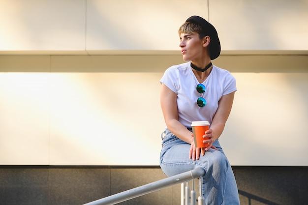 Menina hippie tomando café para ir Foto gratuita
