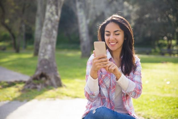 Menina hipster alegre feliz em usar conexão sem fio em parte Foto gratuita