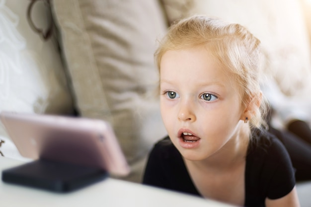 Menina incrível olhar para o telefone. criança assistindo desenhos animados on-line, crianças dependência de computador, conceito de controle parental. Foto Premium