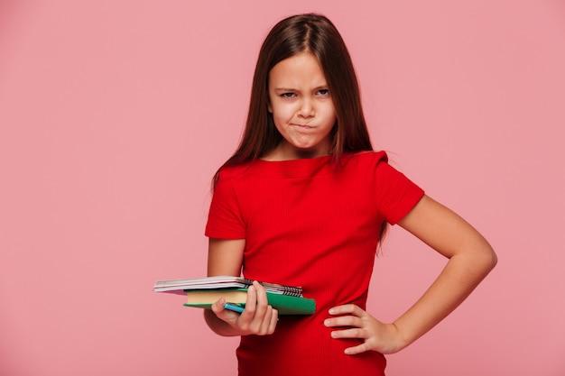 Menina infeliz no vestido vermelho, segurando o livro e olhando Foto gratuita