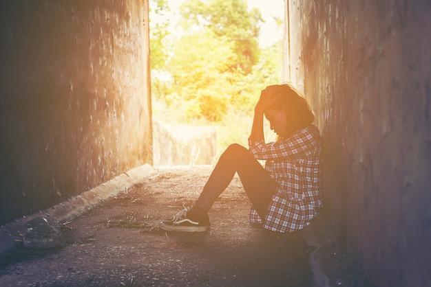 Menina infeliz sentado no chão Foto gratuita