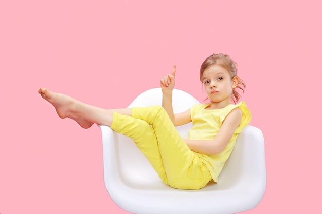 Menina inteligente, apontando para cima em rosa Foto Premium