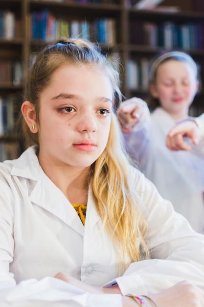 Menina intimidada chorando na biblioteca Foto gratuita