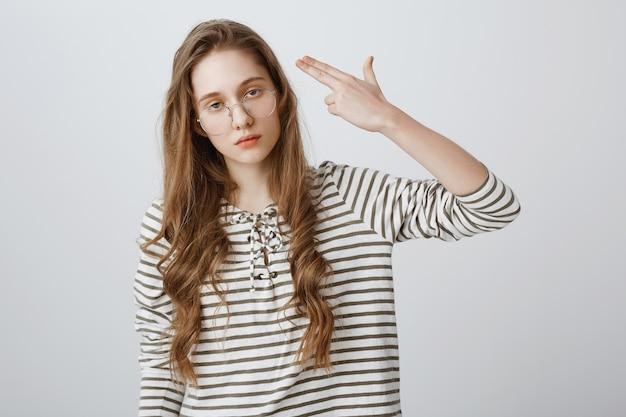 Menina irritada revirando os olhos e atirando em si mesma com gesto falso de arma, enlouquecendo Foto gratuita