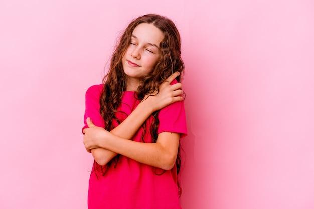 Menina isolada na parede rosa abraços, sorrindo despreocupada e feliz Foto Premium