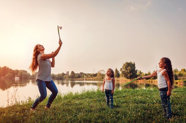 Menina jogando badminton com a irmã no parque de verão Foto Premium