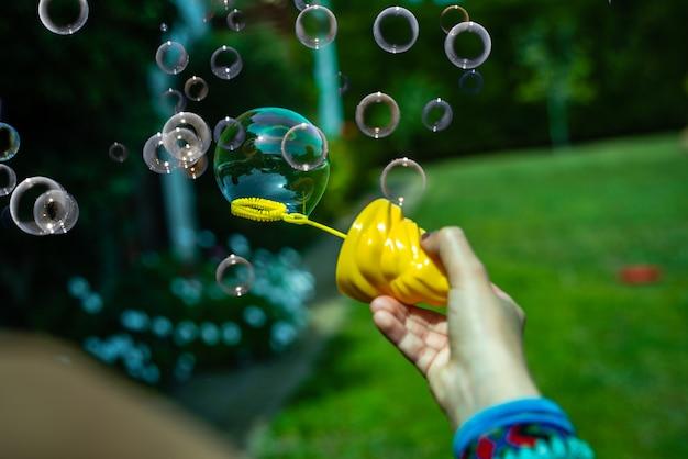 Menina jogando bolhas de sabão no quintal ao sol Foto Premium