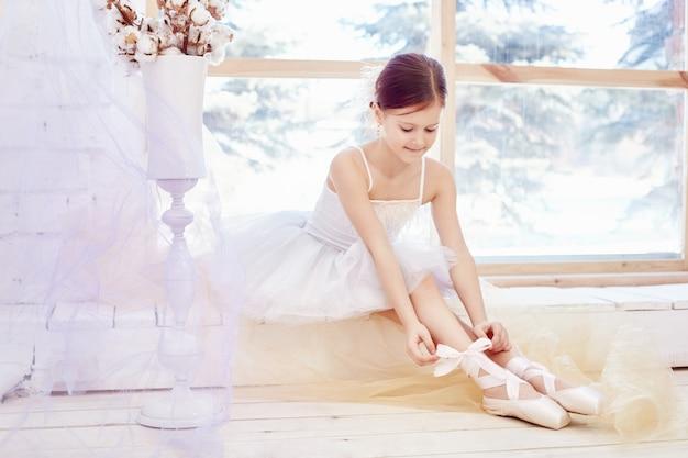 Menina jovem bailarina está se preparando para um balé Foto Premium
