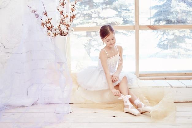 Menina jovem bailarina, preparando o desempenho de balé Foto Premium