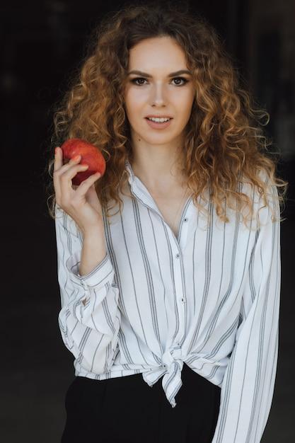 Menina jovem, com, um, maçã vermelha, poses, para, um, foto Foto gratuita