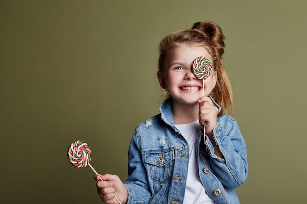 Menina jovem, comer, redondo, doce, licks, pirulito Foto Premium