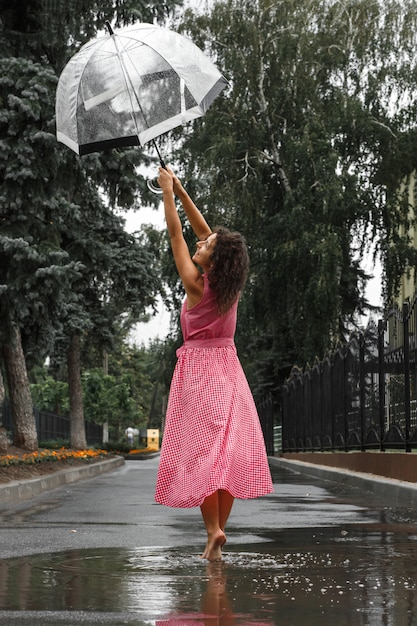 Menina jovem, em, um, vestido vermelho, com, um, guarda-chuva transparente, dançar, em, a, chuva, ficar, em, um, poça Foto Premium