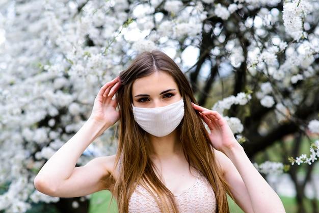 Menina, jovem mulher com uma máscara médica protetora estéril no rosto no jardim primavera. poluição do ar, vírus, conceito de coronavírus pandêmico. Foto Premium