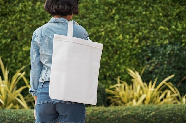 Menina jovem, segurando, branca, tecido, saco, em, parque Foto Premium