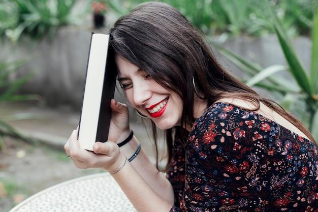 Menina jovem, segurando um livro Foto gratuita
